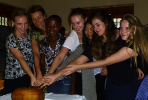 Swedish visitors share with a Kisiizi pupil in cutting a cake