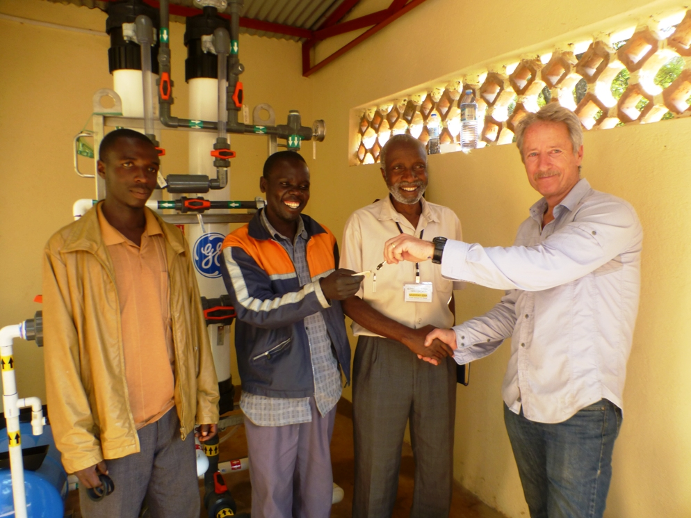 Jim Stunkel of Assist International hands over the key to Ezra & Black